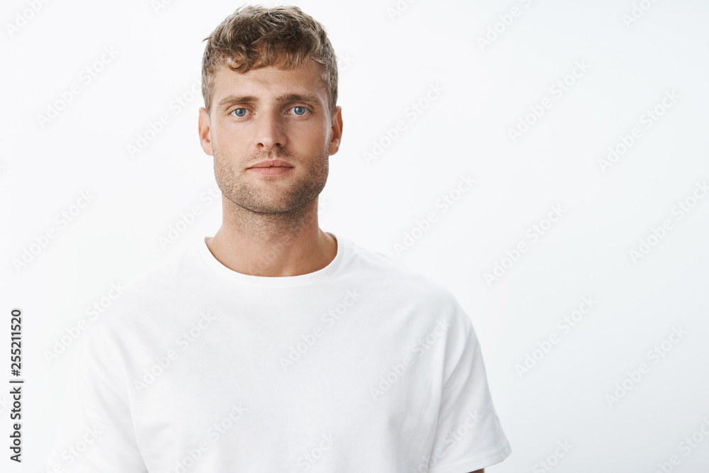 Fototapeta Serious-looking peaceful and calm attractive blond european man with blue eyes and bristle looking at camera focused and chill without emotions, unbothered over gray background in white t-shirt