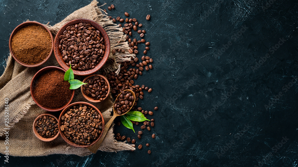 Leinwandbild Motiv - Yaruniv-Studio : Ground coffee and coffee beans. Assortment of coffee varieties on a black background. Top view. Free space for your text.