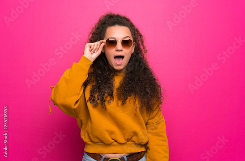 Fotografia  Teenager girl over pink wall with glasses and surprised