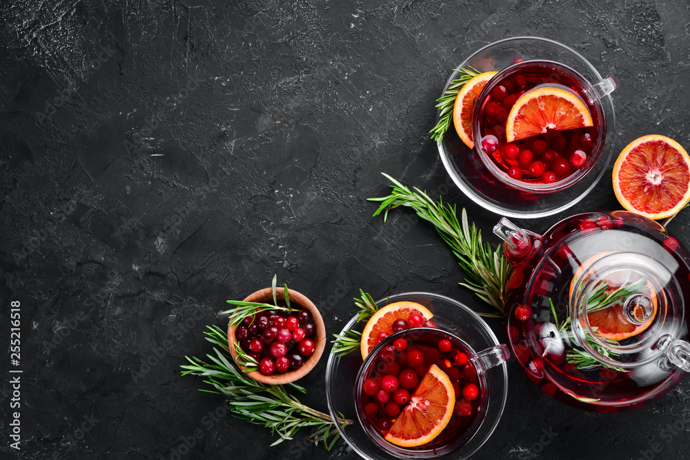 Fototapety, obrazy: Hot tea with berry cranberry and orange. On the black kitchen background. Top view. Free space for your text.