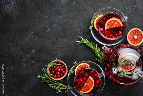 Hot tea with berry cranberry and orange. On the black kitchen background. Top view. Free space for your text.