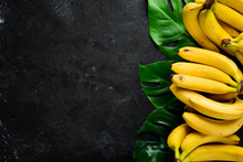 Fresh Yellow Bananas On A Black Stone Table. Top View. Free Copy Space.