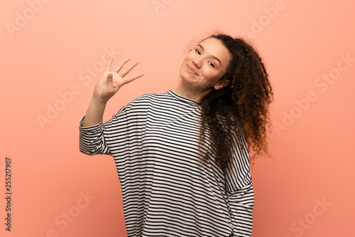 Photographie  Teenager girl over pink wall happy and counting four with fingers