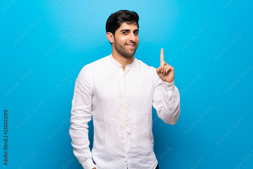 Fototapeta Young man over isolated blue wall showing and lifting a finger in sign of the best