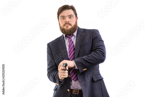 Obraz na plátně  Portrait of a big handsome serious bearded business man with gun in dark suit an