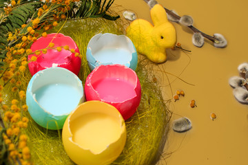 Fototapeta na wymiar Pastel colored easter eggs and bunny in a egg box with a mimosa on yellow background