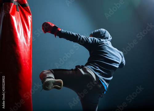 The young man workout a kick on the punching bag Wallpaper Mural