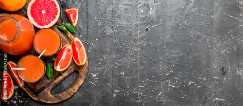 Photo sur Toile Jus, Sirop Juice of ripe grapefruit in a jug on a cutting Board.