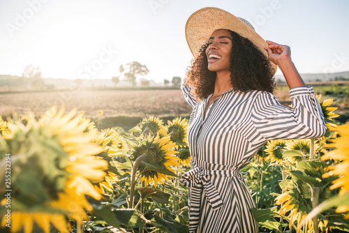 Spoed Foto op Canvas Zonnebloem Happy young black woman in a sunflower field