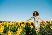 Happy Young Black Woman Walking In A Sunflower Field