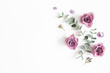 Flowers composition. Pattern made of eucalyptus branches and rose flowers on white background. Flat lay, top view, copy space