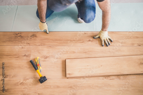 Obraz Professional flooring installation - laying a new laminate with a wooden pattern - fototapety do salonu