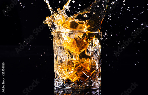 Tableau sur Toile whiskey with splash on black background, brandy in a glass