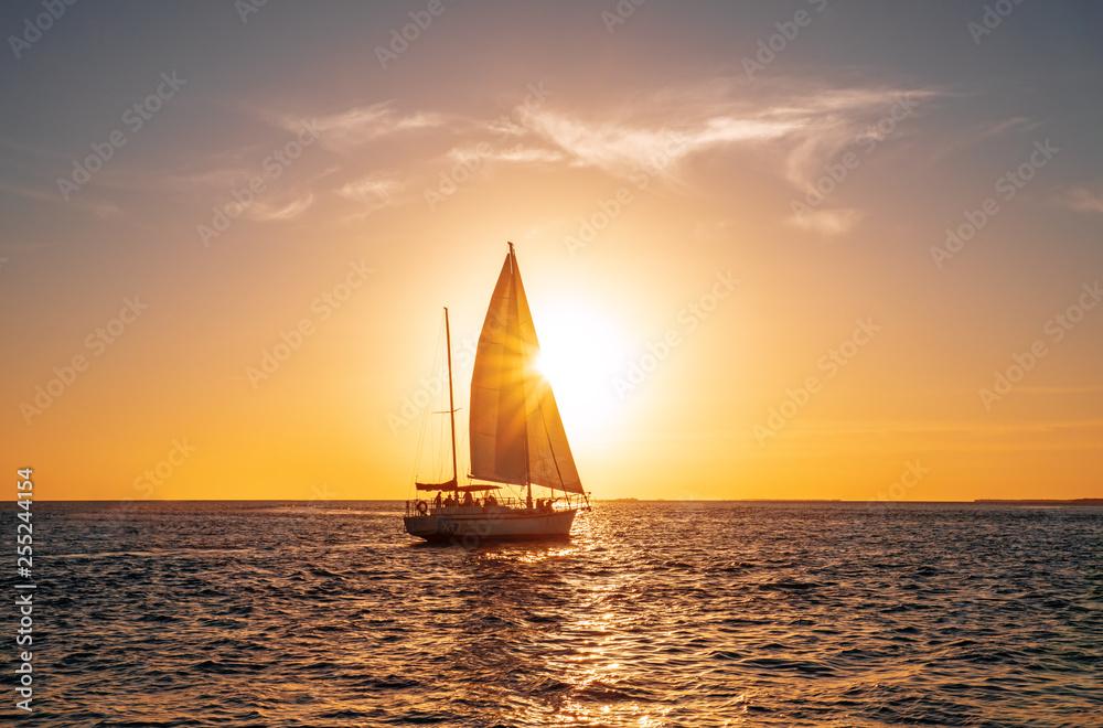 Fototapeta Sailing yacht in the ocean at sunset