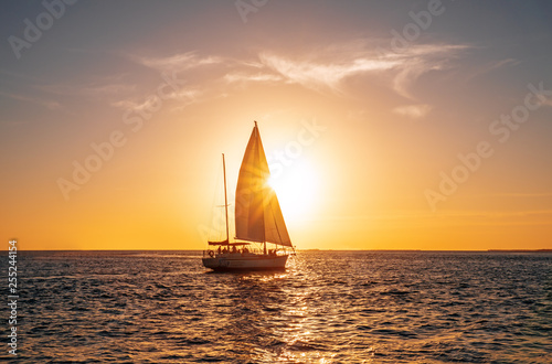Fototapeten See sonnenuntergang Sailing yacht in the ocean at sunset
