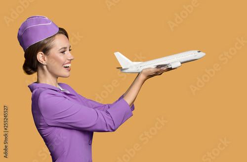 Photo Cheerful stewardess holding airplane in hand.
