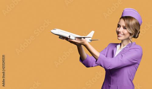 Cheerful stewardess holding airplane in hand. Wallpaper Mural