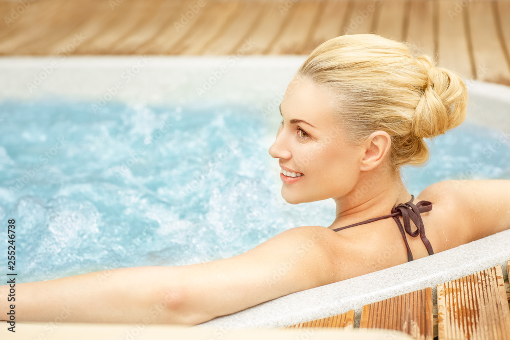Fototapeta She earned this rest. Beautiful woman looking happy relaxing in the Jacuzzi