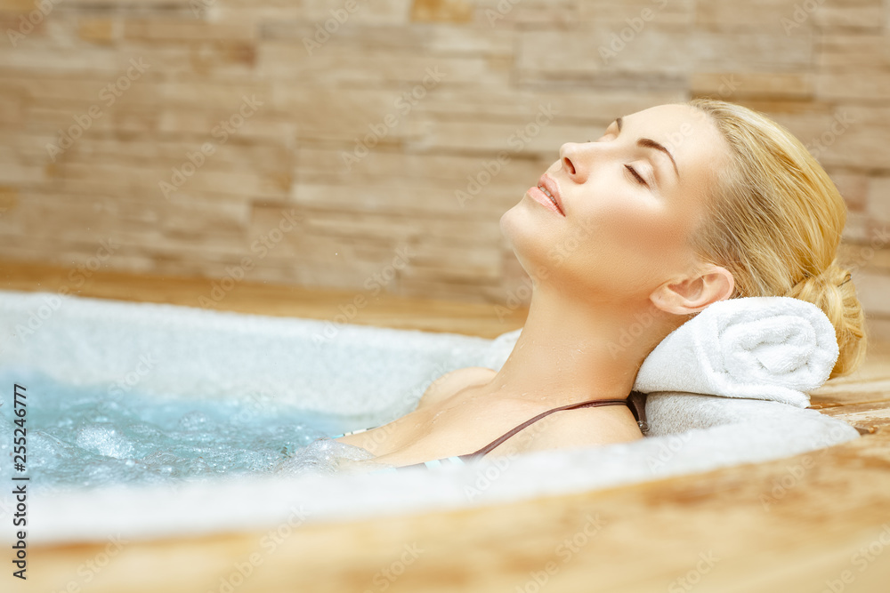 Fototapeta Beauty needs rest. Horizontal shot of a woman enjoying her time in the Jacuzzi with her eyes closed
