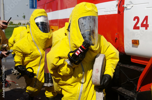 Two firefighters in protective suits and gas masks are preparing for