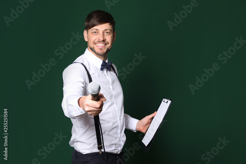 Fotografie, Obraz  Handsome man in formal clothes with microphone and clipboard on color background
