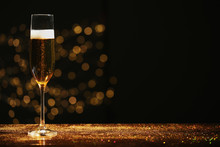 Glass Of Champagne And Golden Glitter On Table Against Blurred Background. Space For Text