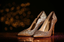 Golden Glitter Shoes On Dark Reflective Surface Against Blurred Background. Space For Text