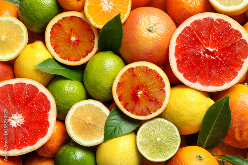 Fényképezés Different citrus fruits as background, top view
