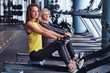 Two beautiful young women doing rowing practice in the modern gym