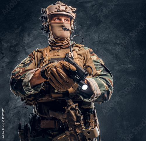 Photo  Elite unit, special forces soldier in camouflage uniform holding a gun with a flashlight and looking sideways