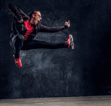 Emotional hip-hop style dancer performing acrobatic elements, jumping and shows the fuck sign. Studio photo against a dark textured wall