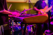 Musician's Hands Playing Keyboard At A Live Show On Stage With Other Men Playing Guitars, The Concept Of Musical Instrument
