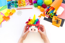 Child Makes A Hand-made Unicorn Out Of A Tin Can. Rainbow Hair