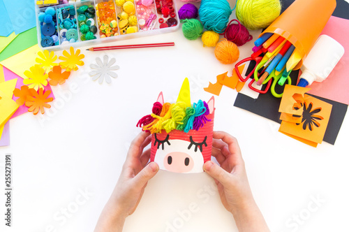 Foto  child makes a hand-made unicorn out of a tin can. Rainbow hair