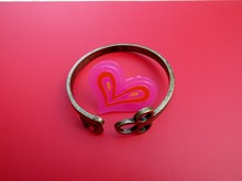 Skeleton Key Cuff Bent Around Pink Heart On Pink Background