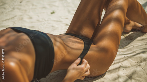 Obraz long-legged model in black bikini is on the ocean beach lying in a sexy pose, - fototapety do salonu