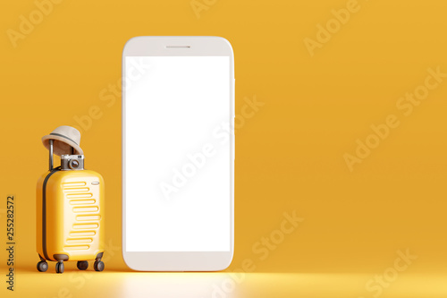 Foto  Suitcase and hat, camera with smartphone on yellow background