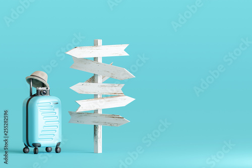 Blue suitcase and hat, camera with signpost on pastel blue background Fototapeta