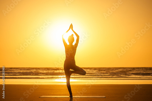 Foto auf AluDibond Orange copyspace woman doing yoga performing asanas and enjoying life at sunset on the beach sea copy space