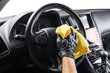 A man cleaning car with yellow microfiber cloth. Car detailing or valeting concept. Selective focus. Car detailing. Cleaning with sponge. Worker cleaning. Car wash concept solution to clean