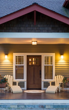 Front Porch And Entry Of Traditional Craftsman Style Home At  Twilight Dusk With Windows, Wooden Front Door, Exterior Lighting And Adirondack Chairs