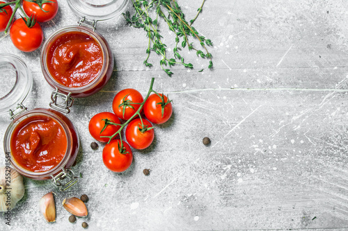 Fototapeta Tomato sauce in a jar of herbs, garlic and cherry. obraz