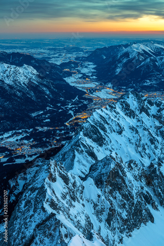 Foto  Tagesanbruch auf dem Gipfel der Zugspitze mit Blick auf das erleuchtete Garmisch