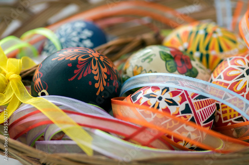 Fotografía  Colorful painted Easter eggs in brown wicker basket covered with colorful ribbon