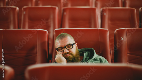 Bearded man with glasses sleeping alone in cinema hall while everyone is gone фототапет