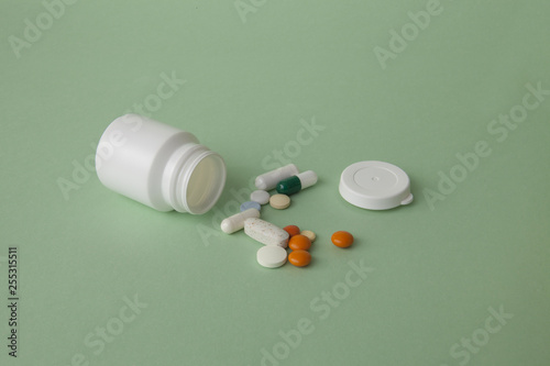 Fotografia  Pills, tablets and capsules and a bottle on a green background