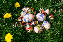 Easter Basket With Cake And Colored Eggs Among Spring Flowers And Grass Blossom. Holiday Cookies With Bright Icing Top For Spring Celebration. Traditional Easter Treat – Sweet Cooking And Painted Eggs