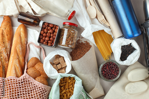 Fotografía  Meal in eco cotton bags, glass and paper packaging on table in the kitchen from market
