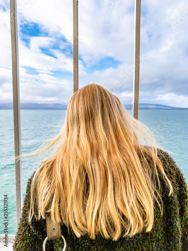 Fotografie, Obraz  Blond Lady looking through the bars and looking to sea and land