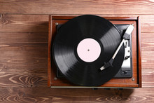 Record Player With Vinyl Disc On Wooden Table